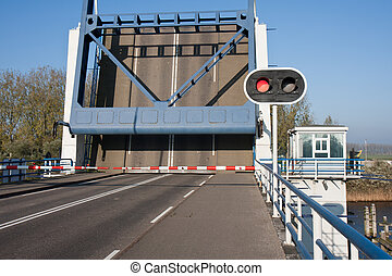 Opened bascule bridge in the Netherlands with red stop sign