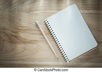 Opened copybook pencil on wooden board