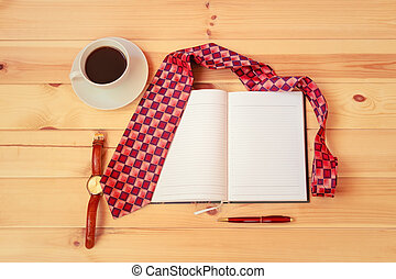 Opened diary, necktie, cup of coffee, watch and pen on wooden table. Top view, copy space.