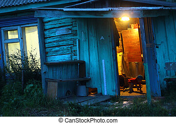 Opened door in night in terrible house with warm light inside. Horror background in night. Warm inside and inviting strangers. Christmas invitation in village house
