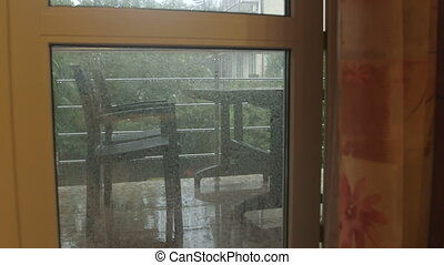 Opened door to balcony in the rain