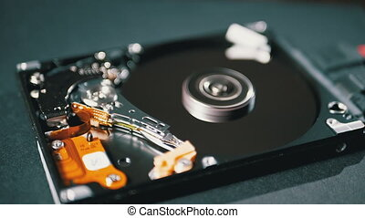 Opened Hard Disk Drive with Spinning Platter. Detail of Working process. Slow Motion in 180 fps. Close-up move of writing magnetic head on actuator arm axis and spindle. Internal Structure HDD. Data storage.