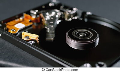 Opened Hard Disk Drive with Spinning Platter. Detail of Working process. Close-up move of writing, reading magnetic head on actuator arm axis and spindle. The Internal Structure of HDD. Data storage.