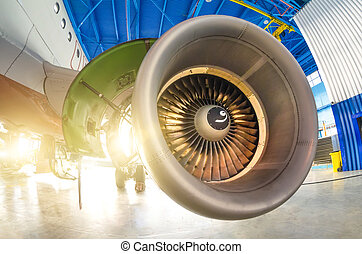 Opened hood aircraft engine in the hangar.