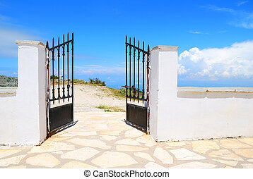 Opened iron gate in a white wall with blue sky behind