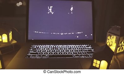 Opened laptop with blinking candles on table