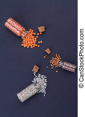 Opened mini glass bottles with spilled out grains.