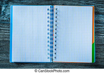 Opened notebook on wooden board