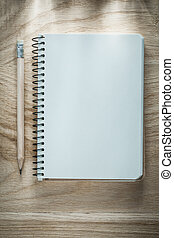 Opened notebook pencil on wooden board