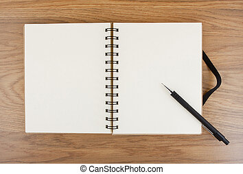 Opened notebook with black elastic band and pencil