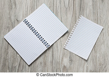 Opened notepad with a sheet of paper on wooden background