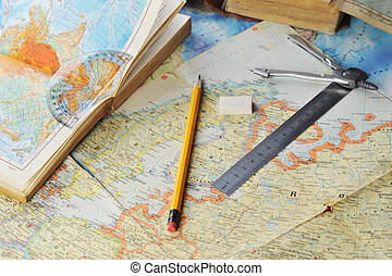 map and pensil - opened old atlas book on map and pensil