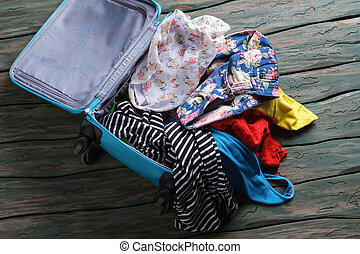 Opened suitcase with clothes.