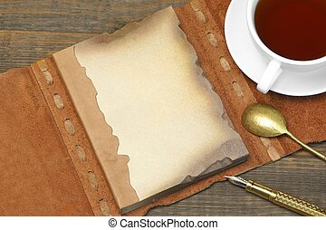 Opened Vintage Notebook With Blank Brown Page And Orange Leather Cover , Golden Fountain Pen, Full Teacup, Retro Golden Spoon On The Rough Rustic Wood Table Background