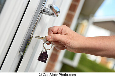 Opening a door to house with key