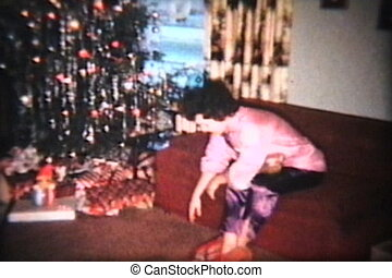 A family spend time together around the Christmas tree opening up gifts and presents to each other. (Scan from archival 8mm film)