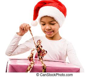 Opening giftbox - Happy girl in Santa cap unwrapping ribbon...