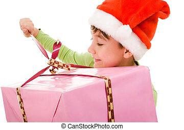 Opening giftbox - Portrait of boy in Santa cap unwrapping...