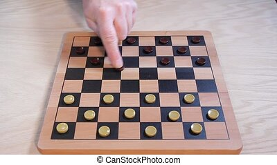 Players making opening moves in a checker game
