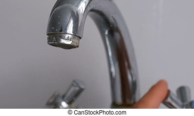 Opening the Faucet and Stream of Water Pouring from Chrome-Plated Tap