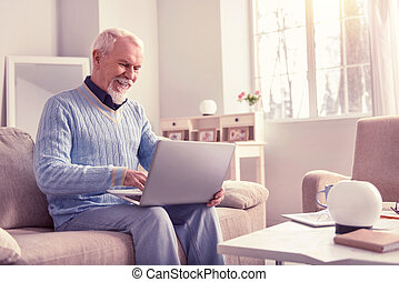 Openly smiling elderly man working with laptop