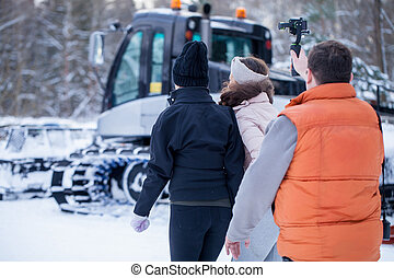 Operator filming the two girls coming forward on snow...