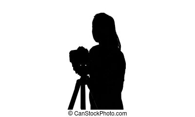 Operator makes shooting in the studio. White. Silhouette
