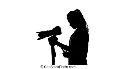 Operator makes shooting with a tripod. White. Silhouette -...