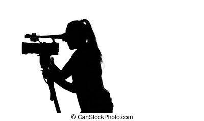 Operator moves the camera. Videography in the Studio. White. Silhouette