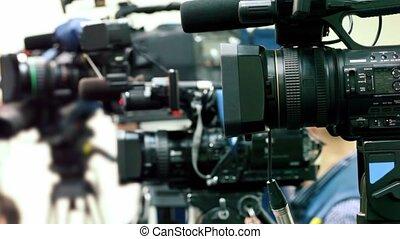 Operator prepare equipment in row of few cameras, second man...