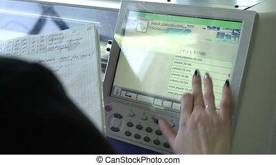 Operator setting knitting machine programme view - Female...