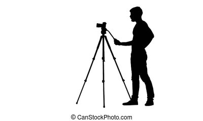 Operator turns the camera on tripod in different directions. Silhouette
