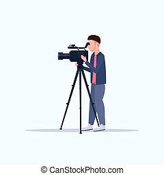 operator using video camera on tripod cameraman looking ...