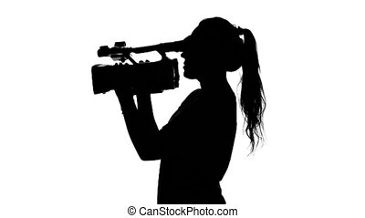Operator walking with camera and shooting a film. White....