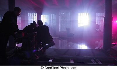 operator with videocamera push on rail cart in dark room