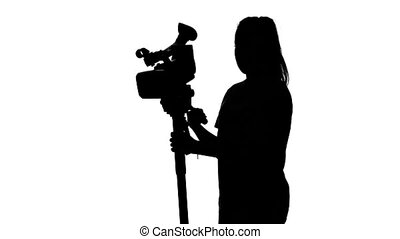 Operator working in the studio with a tripod. White. Silhouette