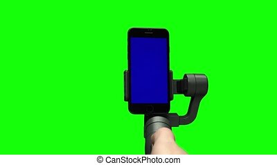Operator's hand controlling steadicam gimbal stabilizer with blue screen on smartphone upright. Professional equipment for the filmmaker making high quality video. Close-up motion on green background.