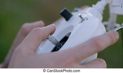 operator's hands hold droning remote controller and using...