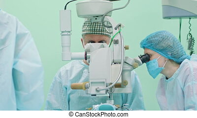 Team of ophtalmology surgeons and assistants with ophtalomological surgery tools during surgical treatment. Female and male surgeons operate the machinery. Indoor. Close up.
