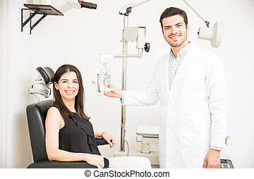 Ophthalmologist in exam room with young woman