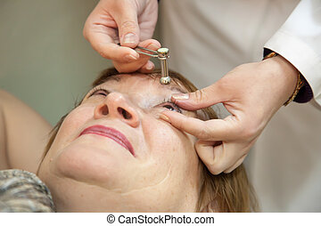 Ophthalmologist measures the ocular tension in patients