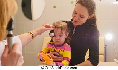 Ophthalmology - doctor checks eyesight at little girl -...