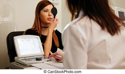Ophthalmology medical, health, concept - beautiful girl checks vision in an ophthalmologist with one eye closed