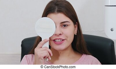 Ophthalmology treatment - young woman checking her visual acuity - closing her eye with an eye shield and saying what the projection says. Mid shot
