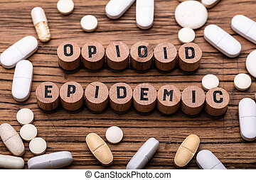Opioid Epidemic Text On Cork With Spilled Prescription Pills Over Wooden Background