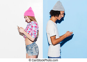 Opposites attract. Funky young couple holding mobile phones and standing back to back while standing against colorful background