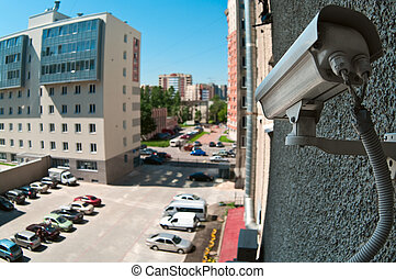 Optical camera on wall of building watching on parking place...