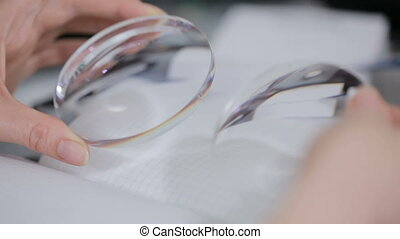 optical round lens in female hands. inspection - optical...