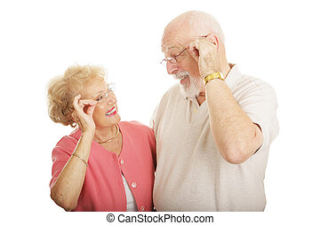 Senior couple smiling and looking at each other's new glasses. Isolated on white.