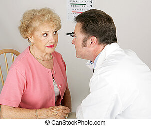 Optician looking into a senior woman's eyes during a routine eye exam.